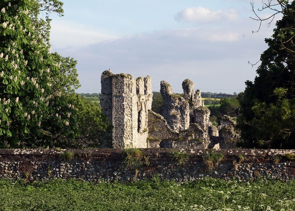 Castle Acre Priory ruins from across a meadow. Peddars Way trail 2018
