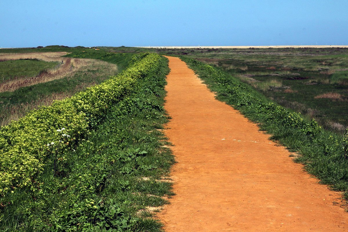 Read earth path stretching across the Norfolk marshes to the horizon. Peddars Way and Norfolk Coast Path National Trail,, 2018