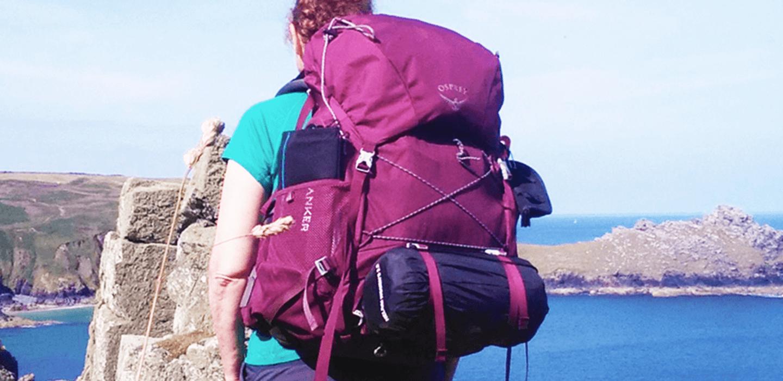 Osprey REnn 65 women's specific rucksack (worn by woman on coast path, seen from behind