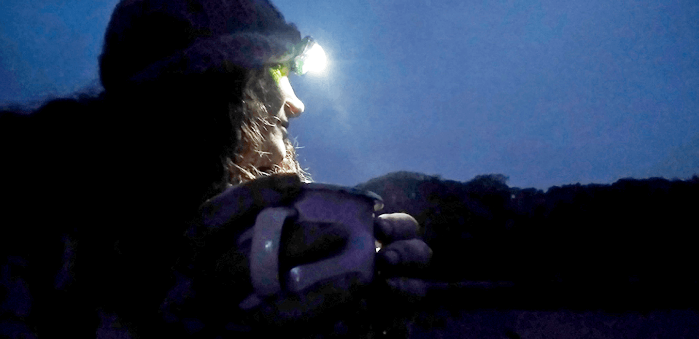 Stephanie Boon wearing a headtorch and holding a mug under a night sky on a bivvy camp