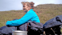 Article: Bivvy Camping For Beginners. Image: Stephanie Boon sitting in a bivvy bag on the grass (side view).