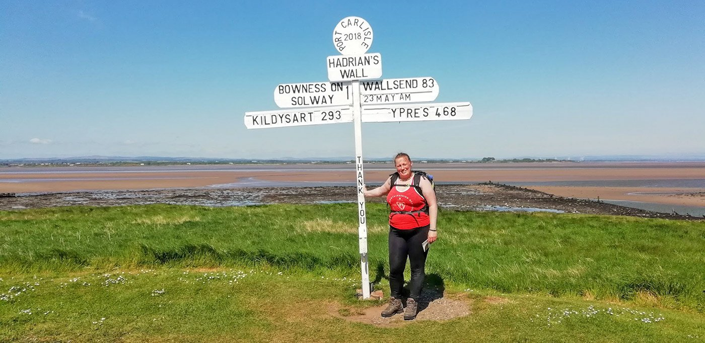 Sarah James, hiker from the NW of the UK beside a finger post on the Hadrian's Wall long distance national trail